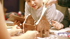 Brother and sister smiling while helping dad build chocolate house Stock Footage