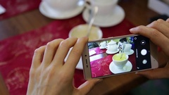 Trendy woman in a restaurant make photo of food with mobile phone camera for Stock Footage