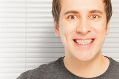 Happy young man with orthodontic cases Stock Photos