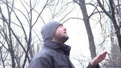 4K winter man in the park enjoying snowfall male catching snowflakes in hand Stock Footage