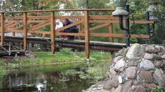 Happy young father with baby daughter admire nature on bridge through river. 4K Stock Footage