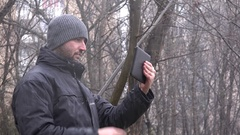 4K business man with tablet in forest woods working snowing weather winter snow Stock Footage