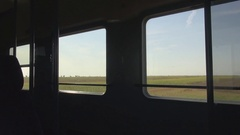 Beautiful commuting scene dark train wagon and sunny green fields outside rails  Stock Footage