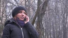 Terrified desperate woman in the park talking on mobile phone fast moving eyes Stock Footage