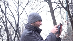 4K winter landscape male in the park sending message to dating girl snow fall Stock Footage