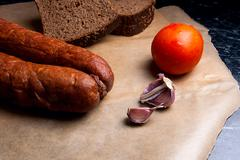 Close up view smoked sausage with spice and vegetables on the packaging paper Stock Photos