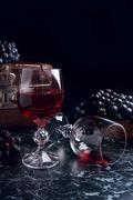 Glass of red wine on dark marble background. Cluster of blue grapes on on b.. Stock Photos