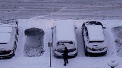 Aerial view of woman cleaning snow and ice off her car wind shield window Stock Footage
