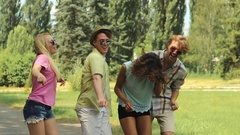 Four young people dancing, jumping to energetic song, throwing hands in air Stock Footage