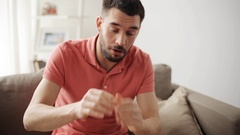 Sick man blowing nose to paper napkin at home Stock Footage