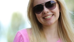 Beautiful blond girl with perfect skin smiling at camera, sunglasses off and on Stock Footage
