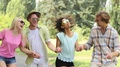 Joyful young people laughing, dancing and jumping high while holding their hands HD Footage