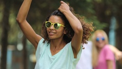 Biracial female artist dancing, singing in front of camera, crowd at background Stock Footage