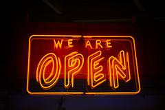 Open neon sign against dark background showing open for business Stock Photos