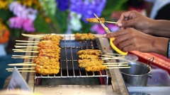 Pork Satay Thai food in local market. Hand using scissor cut burnt part out Stock Footage
