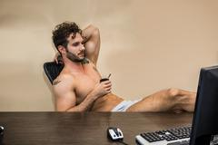 Sexy man sitting topless at office desk with coffee Stock Photos