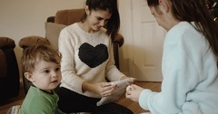 Happy 3 children wrapping Christmas gift for parents near Christmas tree . Cute Stock Footage