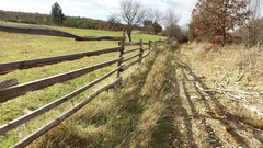 Walking by Beautiful un-paved country road lined with fence, pov Stock Footage