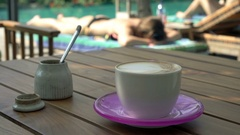 View of cup of coffee on wooden table in outdoor cafe by pool Stock Footage