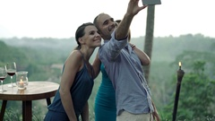 Young friends taking selfie photo with cellphone in outdoor cafe in garden Stock Footage
