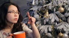 Woman sits near Christmas tree, drinking tea talking indoors Stock Footage