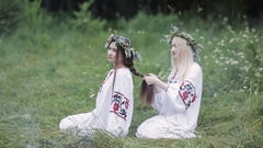 Midsummer. Two girls in the Slavic clothes weave braids in the hair near the Stock Footage