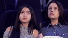 Girls worry about movie characters at the cinema Stock Footage