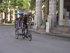 Empty trishaw with cuban flag onto the seats is riding on street of Havan Stock Footage