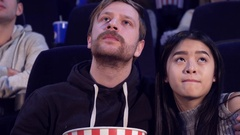 Man embraces his girlfriend at the movie theater Stock Footage