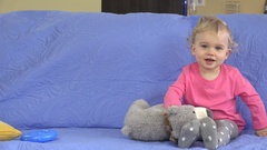 Funny happy toddler girl playing with her toys on sofa Stock Footage