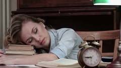 Tired female taking a nap on a pile of books and being woken up by an alarm Stock Footage