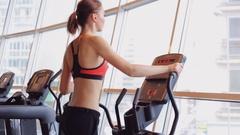 Sports girl doing exercises on the simulator ellipsoid Stock Footage