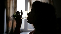 Woman face silhouette drink worm clear water from glass in slow motion Stock Footage
