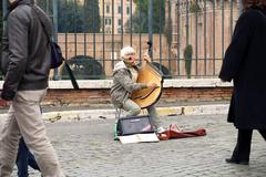 Woman singing and playing harp outdoors on the building site near colosseum in Kuvituskuvat