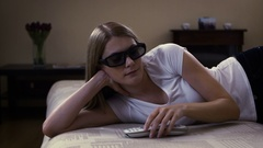 Young beautiful woman lying on a couch. Puts on 3d-glasses switches on smart TV Stock Footage