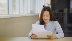 Young beautiful woman examines different documents in office Stock Footage