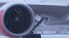 Plane parked at the airport. Ready to fly. The turbine close-up. In winter snow Stock Footage