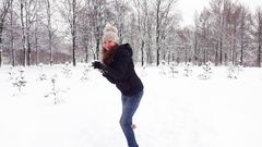 Young woman run towards and strike snow into camera, playful mood Stock Footage