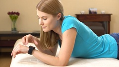 Beautiful attractive young woman lying on sofa and dictating a message on her Stock Footage
