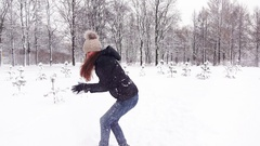 Cheerful woman aim and throw snow to camera, wintery park outdoors Stock Footage