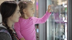 Mother and daughter selecting a snacks at vending machine inside airport Stock Footage