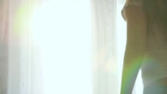 Attractive young woman stretching at the window Stock Footage