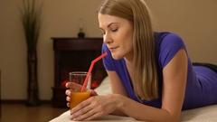 Young attractive beautiful woman lying on a sofa and drinking juice from a glass Stock Footage