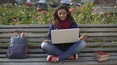 Cute multiracial curly-haired girl in headphones posing for camera and smiling Stock Footage