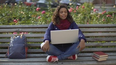 Young excited woman sitting on the bench outdoors  and waiting for her friends Stock Footage