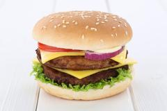 Double cheeseburger hamburger tomatoes lettuce cheese wooden board Stock Photos