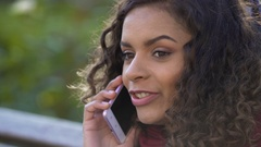 Young attractive female talking with her friend over mobile phone, closeup Stock Footage