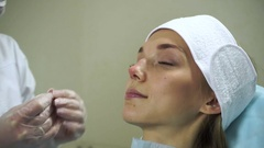 Non-surgical correction of shape of a nose. A young girl during a procedure. HD Stock Footage