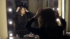 A young girl looks at herself in the mirror at the beauty salon. Stock Footage