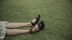 Old footage retro film grain of Asian man is kicking hitting his feet on grass Stock Footage